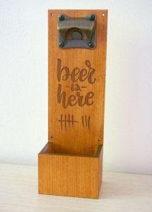 """Dřevěný otvírák lahví na zeď s přihrádkou na vršky """"beer is here"""""""